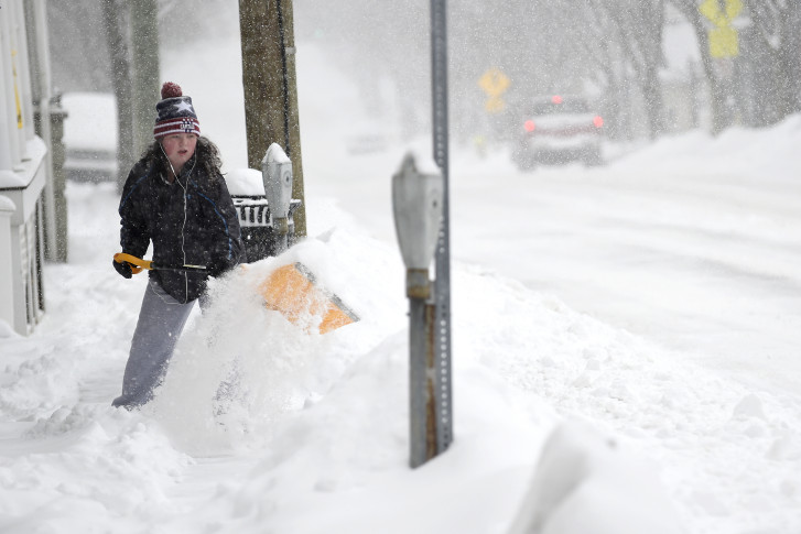 Madison Carter shovels the sidewalk along East Main Street in front of her home as snow falls, Thursday, March 5, 2015, in Westminster, Md. (AP Photo/The Carroll County Times, Dave Munch)