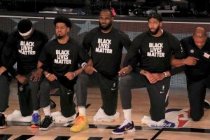 LeBron James and the Lakers players take a knee during the anthem before their game against the Clippers on June 30.
