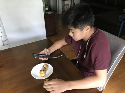 Sophomore Nick Kim on Sept. 9 eats lunch the same way he does at school: ready to listen to music and on his phone. After he eats his lunch he goes outside to see his friends. Photo by Sean Kim.