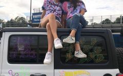 Eleni Jones and Rachel Son sitting on top of one of the cars they painted in their tie-dye senior shirts