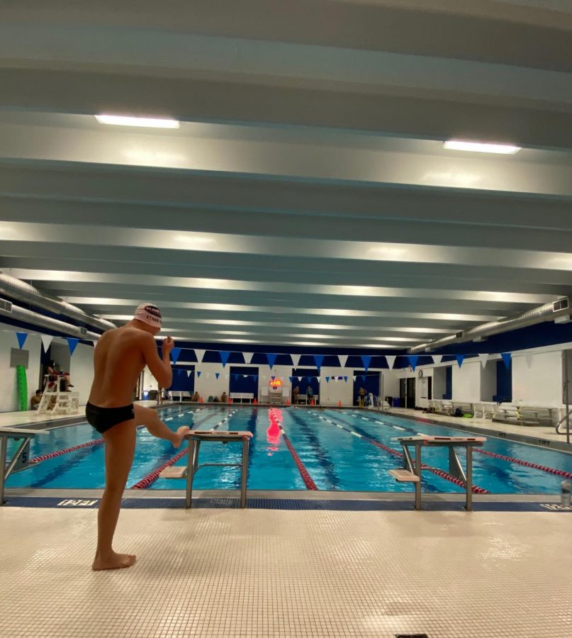 Swimmer gets into his lane by himself for practice.