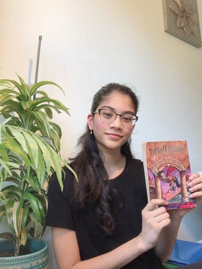 Book club member junior Rashmi Kanipakala displays her favorite book, Harry Potter and the Sorcerer's Stone by J.K. Rowling.