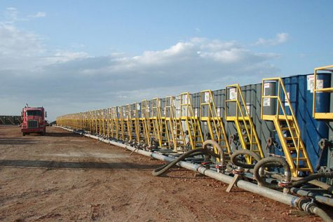The image captured depicts the water consumption of fracking. Hundreds of water tanks are lined up, ready to use.