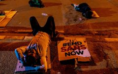 Young Nigerian protesters lay next to their signs, showing  support for the #EndSARS movement.