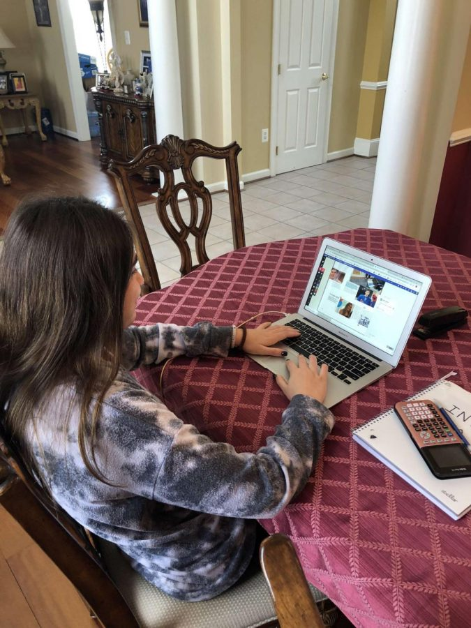 Senior Eleni Jones works on her sports spread in her home on Dec. 18.