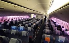 A nearly empty flight, practicing social distancing and mask wearing to prevent the spread of COVID-19.