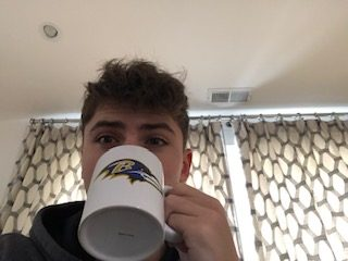 Freshman Joshua Mirsky drinks hot chocolate on a winter day while watching the Baltimore Ravens play.