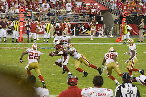 Wide receiver Larry Fitzgerald gets tackled by division rival Patrick Willis as time expires.