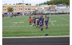 Boys varsity soccer celebrates after winning the Division Championship in 2019 on the schools turf field.