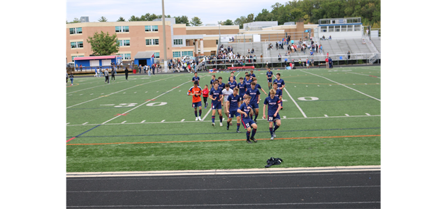 Boys' varsity soccer celebrates after winning the Division Championship in 2019 on the school's turf field.
