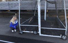 Gillian Berman prepares to carry a field hockey goal with a broken wheel.