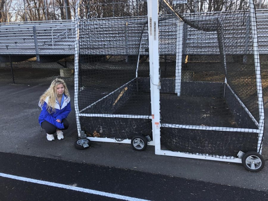 Gillian Berman prepares to carry a field hockey goal with a broken wheel.