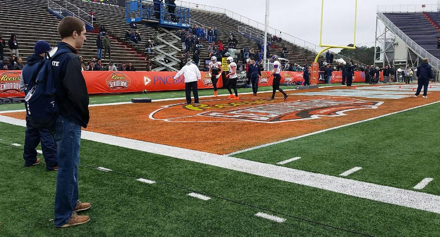 Ryan Stevens a media relations volunteer watches the Senior Bowl practice as part of his job.