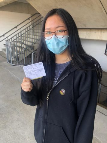 Young-A Kim holds her vaccination card at the exit of the M & T Stadium on Mar. 19.