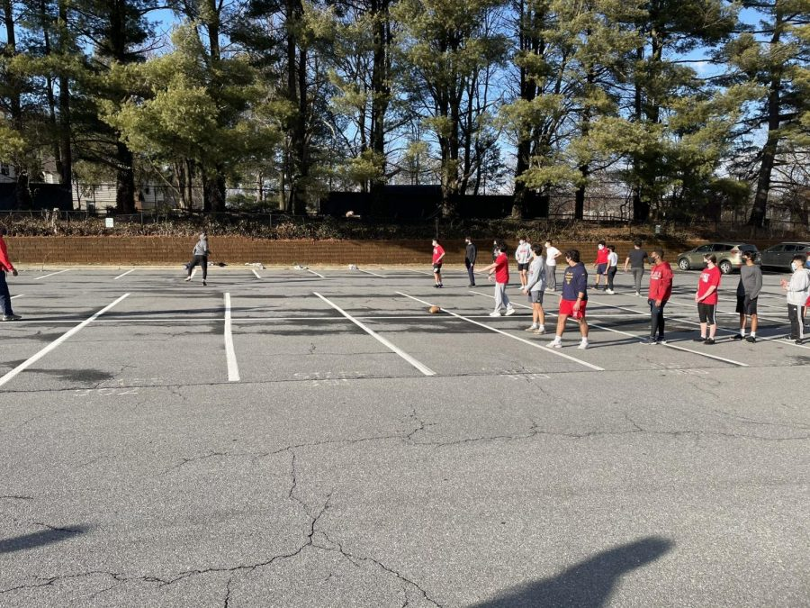 The football team practices plays in the parking lot on Mar. 1.