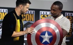 Anthony Mackie and Sebastian Stan observe Captain America's shield.