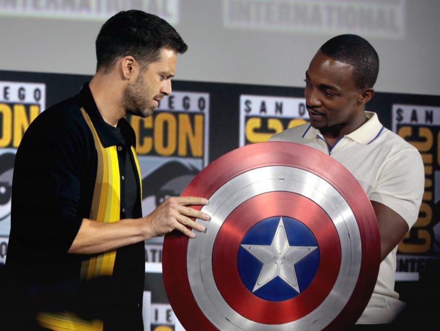 Anthony Mackie and Sebastian Stan observe Captain America's shield.