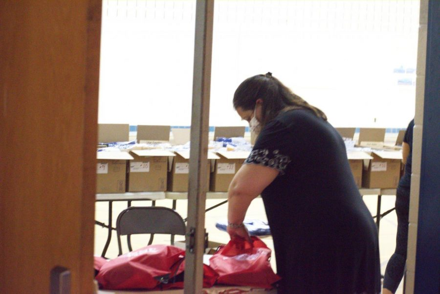 Social studies teacher Christy Rice packs and helps distribute bags with graduation caps, gowns, stoles, ribbons, and more to seniors on May 22 during Unity Day.