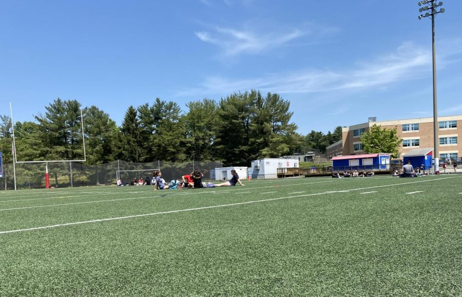Groups of students sit on the turf during lunch.