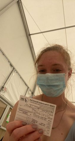 Junior Lizzie Nelson holds her vaccination card after receiving her first Covid vaccine dose.