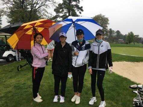 Varsity Golf team members Rita Liu, Chelsea Tu, Rachel Cheung, and Kaleigh Barrow stay dry at the Northwest golf course.