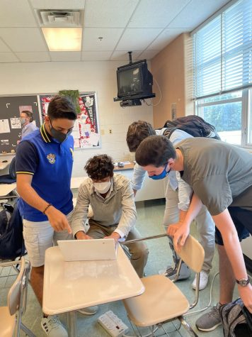 Senior Dylan Safai and juniors Felipe Lemgruber, Zach Haledjian and Ethan Lenkin practice their presentation in AP Lang.