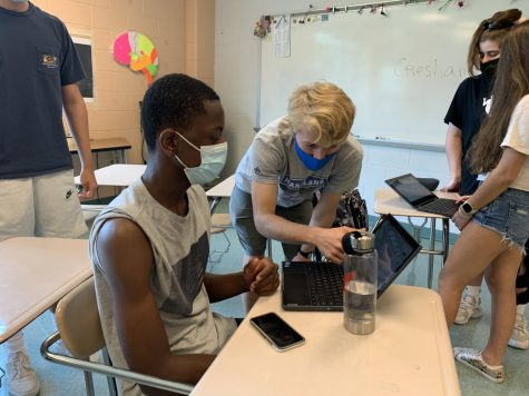 Senior and SGA Co-President Nick Jones helps sophomore Ewere Elbuiazor work on games, tickets and prizes for the Oct. 16 homecoming dance.