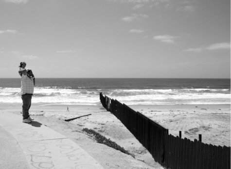 A father and daughter stand on the Mexico side of the U.S.-Mexico border wall.