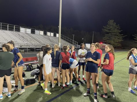 The girls varsity soccer team wraps up a late night practice. Athletes are not required to wear masks outdoors.