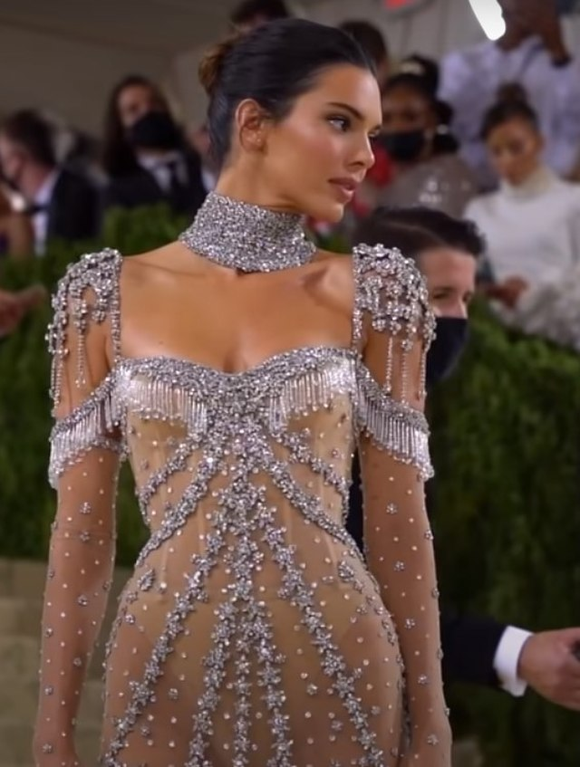 Kendall Jenner, wearing an Audrey Hepburn inspired dress designed by Givenchy, poses on the steps at the 2021 Met Gala.